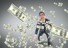 Excited business man looking at money rain against grey background Stock Photo