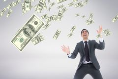 Excited business man looking at money rain against white background Royalty Free Stock Photo