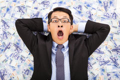 Excited  business man lying on the new taiwan dollar Stock Photography
