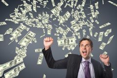 Excited business man with money rain against blue background