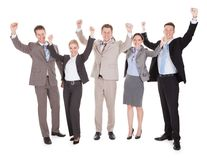 Excited business people cheering over white background Royalty Free Stock Photography