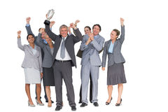 Excited business team cheering at camera with trophy Royalty Free Stock Photo