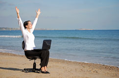 Excited business woman. Young business woman cheering at laptop on the beach Stock Photography