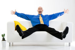 Excited businessman. Sitting on couch with arms and legs stretched Royalty Free Stock Image