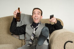 Excited Businessman. An excited businessman kicking and cheering at something he is watching on tv Stock Photo