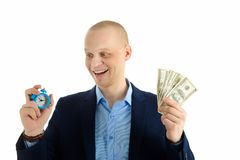 Excited Businessman with alarm clock and stack of cash in hand. Choosing between time and money. Excited Businessman with alarm clock and stack of cash in hand Stock Photos