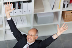 Excited Businessman With Arms Raised In Office Stock Images