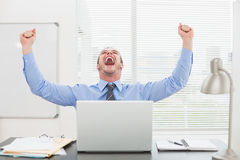 Excited businessman with arms up cheering. In his office Stock Photos
