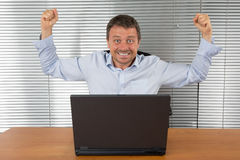Excited businessman with arms up. Cheering in his office Stock Photo