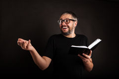 Excited Businessman with beard and glasses. Holding notebook on black isolated background Royalty Free Stock Photography