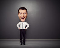 Excited businessman with big head. Full-length picture of excited businessman with big head over dark background Royalty Free Stock Photo
