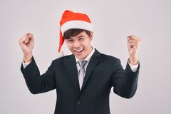 Excited businessman in black suit and santa hat isoalted on whit. E Stock Photos
