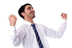 Excited businessman celebrates by pumping fists Royalty Free Stock Photography