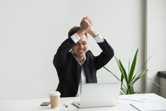 Excited businessman celebrating online lottery win. Happy excited businessman raising hands up celebrating online lottery win, gaining profit, reading good news stock photos