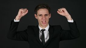 Excited businessman celebrating success, dark black background stock footage