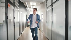An excited businessman dancing in office corridor stock footage