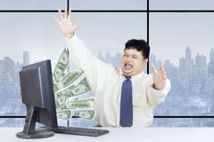 Excited businessman get money from internet Stock Image