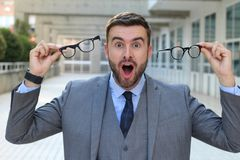 Excited businessman holding two pair of eyeglasses royalty free stock photo