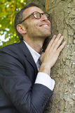 Excited businessman hugging a tree for vitality and energy Royalty Free Stock Photo