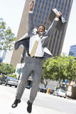Excited Businessman Jumping. An African American excited businessman jumping with hands raised Royalty Free Stock Images