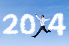 Excited businessman jumping with 2014. On the blue sky Stock Images