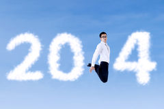Excited businessman jumping with clouds of 2014. Excited asian businessman is jumping with clouds of 2014 on the blue sky Royalty Free Stock Image