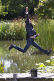 Excited businessman jumping high for success near water in park Royalty Free Stock Photo