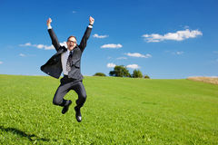 Excited businessman jumps high in the air. Cheering and celebrating a success or achievement in a green sunny field under a blue sky Stock Photography