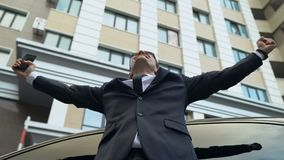 Excited businessman keeping arms raised and expressing positivity outdoors. Stock footage stock video footage
