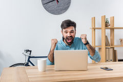 Excited businessman looking at laptop at workplace in office. Portrait of excited businessman looking at laptop at workplace in office Stock Photography