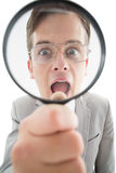 Excited businessman looking through magnifying glass Royalty Free Stock Images