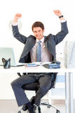 Excited businessman in office rejoicing success. Excited modern businessman sitting at office desk and rejoicing his success Royalty Free Stock Photos