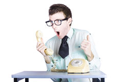 Excited businessman with phone. Portrait of nerdy young businessman shouting into receiver of retro telephone, white background Stock Image