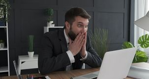 Excited businessman working on laptop. Excited businessman receiving good news on laptop at office stock footage