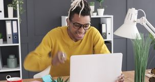 Excited businessman receiving good news while working on laptop. Excited businessman working on laptop and celebrating online success at office stock video