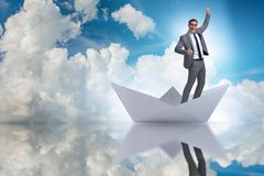 The excited businessman riding paper ship boat Royalty Free Stock Image