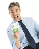 Excited Businessman Showing Euro Banknotes. Portrait of excited mature businessman showing euro banknotes while standing against white background Stock Images