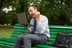 Excited businessman sitting on a bench in park with laptop. stock image