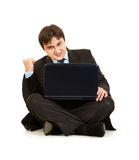 Excited businessman sitting on floor with laptop Stock Photography