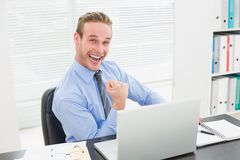 Excited businessman sitting at his desk cheering Royalty Free Stock Photo