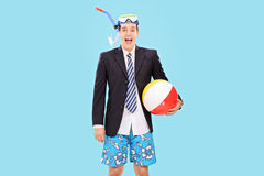Excited businessman with snorkel and a beach ball. Excited businessman with a snorkel holding a beach ball on blue background Royalty Free Stock Image