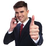 Excited businessman speaking on the phone and making ok sign. Portrait of excited businessman speaking on the phone and making ok sign while standing on white Stock Photography