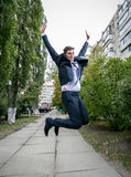 Excited businessman in suit jumping on street Stock Images