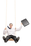 Excited businessman swinging on a swing Royalty Free Stock Photography