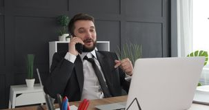 Businessman talking on mobile phone. Excited businessman talking on mobile phone at office stock video footage