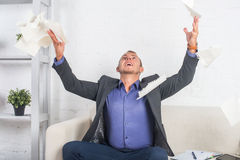 Excited businessman throwing papers at the office Royalty Free Stock Photography