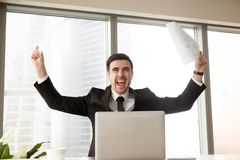 Business leader excited because of great success. Excited businessman waving business papers in hands and screaming loudly with joy at desk in office. Happy boss Stock Images