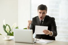 Employee happy of promotion or salary increase. Excited businessman yelling with joy when reading important written notification or letter at desk in office stock photography