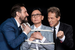 Excited businessmen tying scared asian businesswoman with rope Royalty Free Stock Image