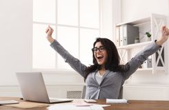 Excited Businesswoman Celebrating Success With Raised Hands At Workplace. Excited Businesswoman Celebrating Success At Workplace, Raising Hands And Looking At stock photography